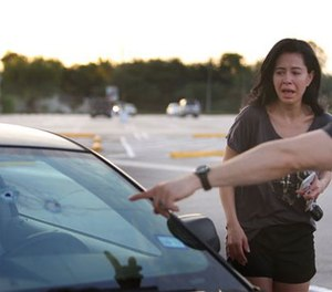 Alan Wakim shows his wife, Jennifer Molleda, where two bullets entered his windshield and went past his face during a shooting along Wesleyan at Law Street in Houston that left multiple people injured and the alleged shooter dead, Sunday morning, Sept. 25, 2016, in Houston. (Mark Mulligan/Houston Chronicle via AP)