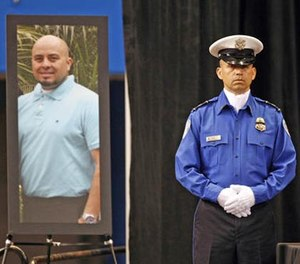In this Nov. 12, 2013 file photo, a Transportation Security Administration officer stands in front of a portrait of slain TSA officer Gerardo Hernandez during his public memorial at the Los Angeles Sports Arena. (Al Seib/Los Angeles Times via AP Pool, File)