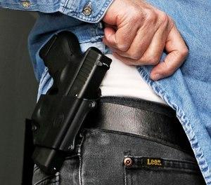 In this Feb. 27, 2013 file photo Hank Johnson displays his handgun, in Springboro, Ohio. (AP Photo/Al Behrman, File)