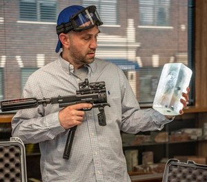 Kurt Boeker points one of the paintball guns that fire less lethal projectiles at a gel designed to absorb the projectiles.