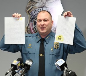 Anne Arundel County Police Chief Timothy Altomare holds up letters written to Detective William Ballard and Detective Ian Preece, who were shot last week by a fleeing suspect. (Photo/TNS)