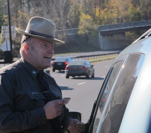 New York State Trooper Clayton Howell checks a driver's license after making a traffic stop for distracted driving in Greenburgh, N.Y., on Thursday, Nov. 14, 2013. (AP Photo/Jim Fitzgerald)
