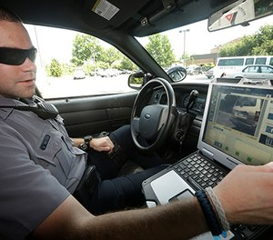 In this July 16, 2013, file photo, Officer Dennis Vafier, of the Alexandria Police Department, uses a laptop in his squad car to scan vehicle license plates during his patrols in Alexandria, Va. (AP Photo/Pablo Martinez Monsivais, File)