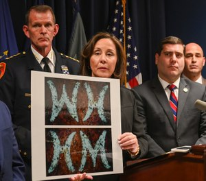 Suffolk County Police Commissioner Geraldine Hart shows a photograph with the initials on a belt, showing either an HM or WH, depending on the angle, during a press conference at police headquarters in Yaphank , N.Y. (Photo/AP)