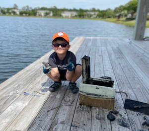 Knox Brewer poses next to a safe he pulled out of Whitney Lake in South Carolina. (Photo/AP)