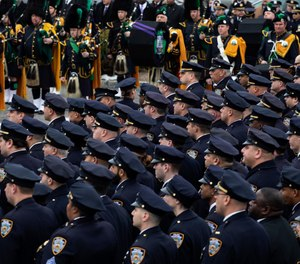 Police officers and a bagpipe band stand at attention during the funeral for Det. Brian Simonsen at the Church of St. Rosalie in Hampton Bays, N.Y., Wednesday, Feb. 20, 2019. (AP Photo/Mark Lennihan)