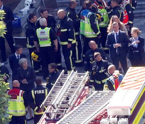 Britain's Prime Minister Theresa May, bottom left, speaks to firefighters and police officers after arriving at Grenfield Tower in London. (AP Photo/Frank Augstein)