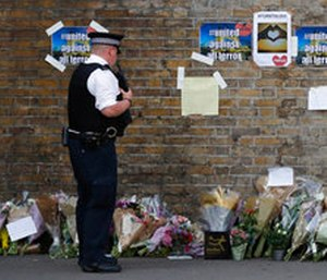 A police officer stands near floral tributes in Finsbury Park after an incident where a van struck pedestrians.