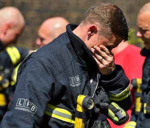 A firefighter puts his hand to his face as he looks at the floral tributes before a minute's silence near to Grenfell Tower.