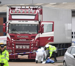 Police and forensic officers at the Waterglade Industrial Park in Grays, Essex, England after 39 bodies were found inside a truck on the industrial estate.