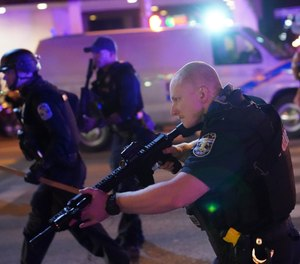 Police move after a Louisville Police officer was shot, Wednesday, Sept. 23, 2020, in Louisville, Ky. (AP Photo/John Minchillo)