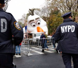 Police officers stand near the site where a large balloon of Olaf, from the animated film,