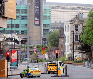Police block roads near to the Manchester Arena, seen at the right, in central Manchester, England.