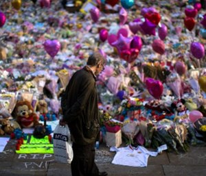 A man stands next to flowers for the victims of the bombing at St Ann's Square in central Manchester, England, Friday, May 26 2017.