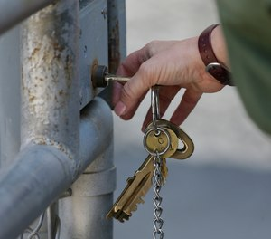 A CO uses a key to open a gate to an exercise yard on death row at San Quentin State Prison Tuesday, Aug. 16, 2016, in San Quentin, Calif. (AP Photo/Eric Risberg)