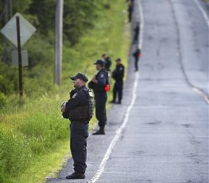 New York State corrections officers line the edge of the forest along County Route 41 in the town of Malone, N.Y. Friday evening, June 26, 2015.