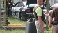 Robbery suspect, handcuffed behind back, steals police car