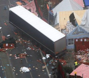 In this Dec. 20, 2016 file photo the trailer of a truck stands beside destroyed Christmas market huts in Berlin, Germany the day after a truck ran into a crowded Christmas market and killed several people.