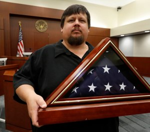 Gary Hulsey, a 40-year-old resident of Wylie, Texas, holds a folded flag that was presented to him at the United States Courthouse in Plano, Texas, Friday, July 26, 2019. (AP Photo/Tony Gutierrez)