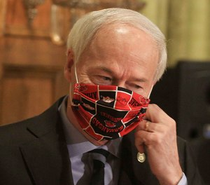 In this April 27, 2020 file photo, Gov. Asa Hutchinson takes off his Arkansas Razorbacks facemark as he arrives for the daily coronavirus briefing at the state Capitol in Little Rock.