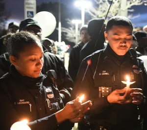 Detroit police officer Devon Leonard, left, relights the candle held by fellow officer Derrick Daniel, right, at a vigil for officer Rasheen McClain Monday night. (Photo/TNS)