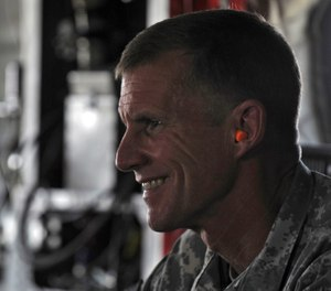 General Stanley McChrystal wears earplugs as he leaves by helicopter after a meeting between President Hamid Karzai and tribal leaders in Kandahar city, Afghanistan, Sunday June 13, 2010. (AP Photo/Massoud Hossaini, Pool)