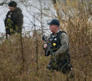 Anne Arundel police search the waters edge in the Stoney Beach community. The manhunt continues for a suspect in the shooting of two Anne Arundel police officers. (Photo/TNS)