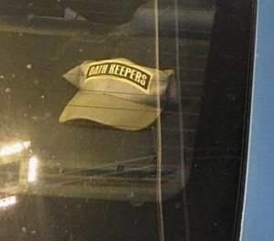 An Anne Arundel police officer has been suspended for displaying a hat bearing the name of a controversial group in the rear windshield of a police cruiser.