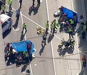 Emergency medical workers offer aid to victims struck by a vehicle in Melbourne, Australia. (Australian Broadcast Corp. via AP)