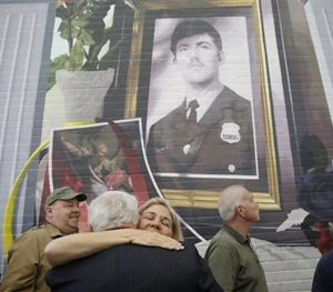 Maureen Faulkner, widow of slain Philadelphia police officer Daniel Faulkner, embraces Joe McGill who prosecuted Mumia Abu-Jamal for the murder of her husband, underneath a new mural of him, Monday, Nov. 24, 2014, in Philadelphia. (AP Image)