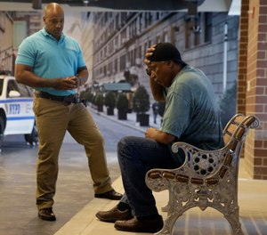 In this Sept. 2, 2015 file photo, New York City Police Officer Lamont Edwards talks to actor Nathan Purdee during a Crisis Intervention Training class at the New York Police Department Police Academy, in New York.