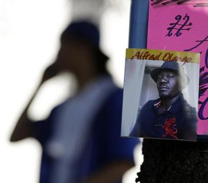 In this Sept. 28, 2016 file photo, a man stands behind a picture of Alfred Olango during a protest, in El Cajon, Calif. (AP File Photo/Gregory Bull)