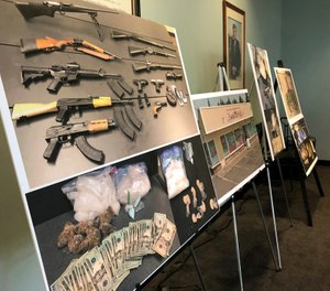 Photos of guns, drugs, and money are displayed at a news conference, Wednesday, Oct. 2, 2019, in Portland, Ore. (AP Photo/Gillian Flaccus)