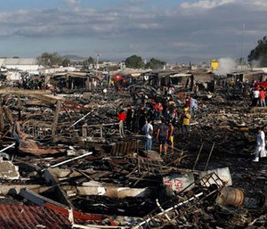 Firefighters and rescue workers walk through the scorched ground of Mexico's best-known fireworks market after an explosion explosion ripped through it, in Tultepec, Mexico, Tuesday, Dec. 20, 2016. (AP Photo/Eduardo Verdugo)