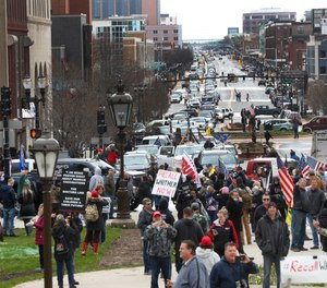 Flag-waving, honking protesters drove past the Michigan Capitol on Wednesday to show their displeasure with Gov. Gretchen Whitmer's orders to keep people at home and businesses locked during the COVID-19 outbreak. (Photo/AP)