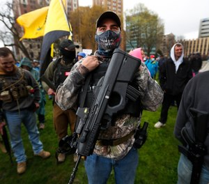 A protester carries his rifle at the State Capitol in Lansing, Mich., Thursday, April 30, 2020.