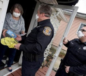 Luna Pier Police Reserve Officers Keith Blosser and Kenneth Mentel delivers Rosanne Metcalf her prescription medicine and light bulbs. (Photo/TNS)