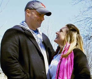 In this Tuesday, March 18, 2014 photo, Boston Marathon bombing survivor Roseann Sdoia stands with her boyfriend, Boston firefighter Mike Materia, after her doctor's appointment in Newton, Mass.