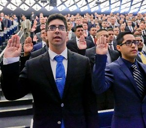New York Police Department (NYPD) recruits raise their right hands in a pledge during a swearing-in ceremony for new recruits at the Police Academy, Thursday, July 6, 2017, in New York.