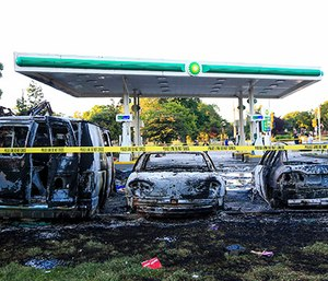Burnt cars sit in the parking lot of a gas station that was destroyed during protests Aug. 14, 2016, following a fatal police-involved shooting the day before in Milwaukee, Wis. (Photo/Armando L. Sanchez/Chicago Tribune)
