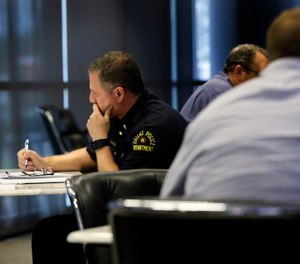 "In this June 22, 2017, photo, Dallas police Lt. Michael Igo, left, contemplates his response to a task as he and fellow officers participate in a training session at the Center for Brain Health in Dallas. Only hours after the ambush that killed five Dallas law enforcement officers July 7, 2016, mental health experts began thinking ahead, searching for ways to ease the long-term effects of the attack on the men and women who patrol the nation's ninth-largest city. Scores of them have received or are on track to receive specialized training in ""mindfulness"" and other stress-management techniques. (AP Photo/Tony Gutierrez)"