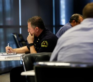 "In this June 22, 2017, photo, Dallas police Lt. Michael Igo, left, contemplates his response to a task as he and fellow officers participate in a training session at the Center for Brain Health in Dallas. Only hours after the ambush that killed five Dallas law enforcement officers July 7, 2016, mental health experts began thinking ahead, searching for ways to ease the long-term effects of the attack on the men and women who patrol the nation's ninth-largest city. Scores of them have received or are on track to receive specialized training in ""mindfulness"" and other stress-management techniques."