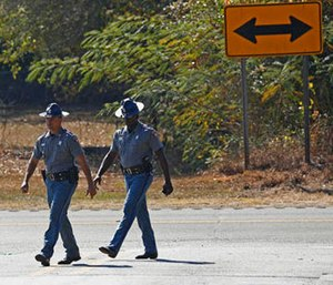 Mississippi Highway Patrol troopers walk along U.S. Highway 80 in Chunky, Miss., Tuesday, Nov. 1, 2016, where authorities say on Monday night, a pickup truck slammed into a small utility trailer carrying a group of trick-or-treaters.