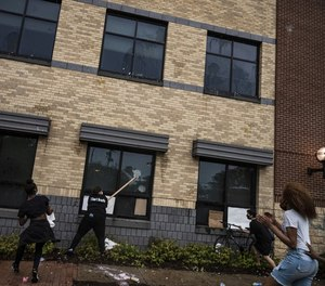 Protesters attempt to damage a police building in Minneapolis during demonstrations following the death of George Floyd.
