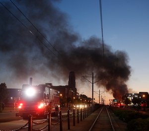 Fire burns during protests over the death of George Floyd, a black man who died in police custody. (AP Photo/John Minchillo)