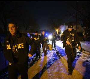Members of the Saint Paul Police Department's gang unit, including Sgt. Shawn Campbell, left, and officer Colby Bragg, right, returned to their cars after executing a search warrant Wednesday night in the Central District which was related to a recent shooting. (Photo/TNS)