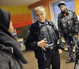 In a photo made Friday, Jan. 14, 2011, Minneapolis police officer Jeanine Brudenell talks with Somali young people in Minneapolis, Minn., who were on hand to sign up for a Minneapolis Police Department Citizens Academy geared toward keeping Somali kids out of gangs . (AP Photo/Jim Mone)