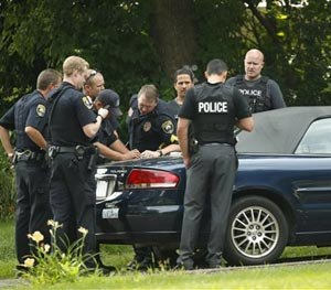 Police officers confer in the driveway of a home in Mendota Heights, Minn., Wednesday afternoon, July 30, 2014.