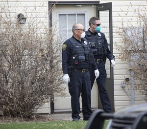 Two Brooklyn Park police officers stand outside a home during a welfare check. Minneapolis police Chief Medaria Arradondo said Monday that all officers will be expected to wear protective masks after the department saw its first case of COVID-19. (Photo/TNS)