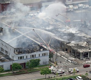 Firefighters work on an apartment building under construction, Thursday, May 28, 2020, tentatively known as Midtown Corner, left, after it was burned to the ground in Minneapolis, Minn. during protests. (Brian Peterson/Star Tribune via AP)